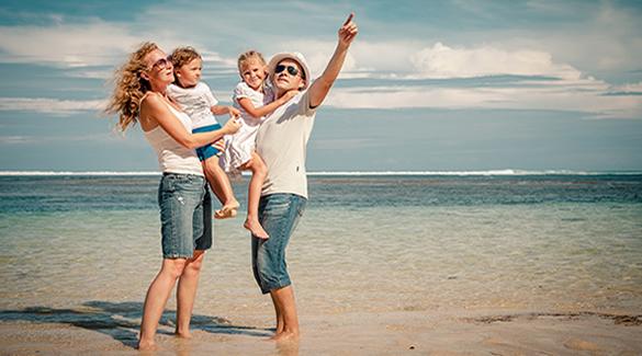 Szczęśliwa rodzina z dzieckiem przebywająca na plaży podczas służbowego wyjazdu firmowego.